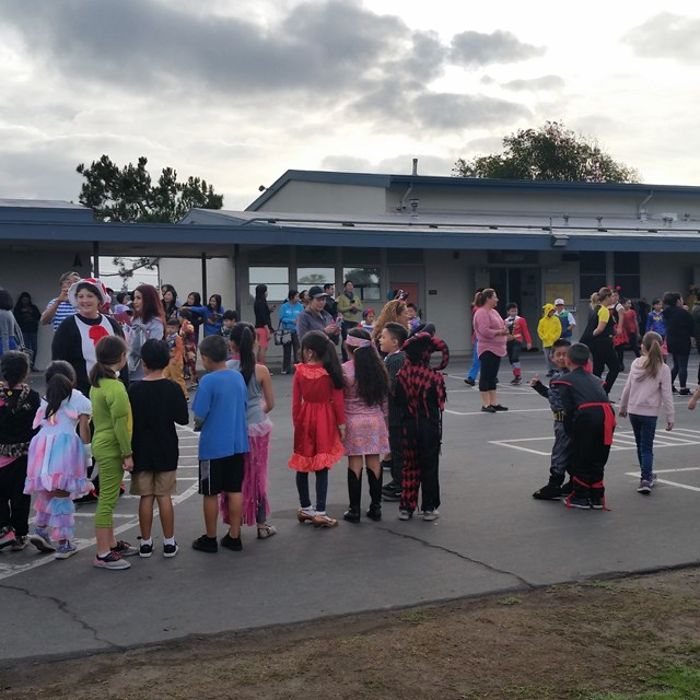 Students show their costumes to each other during recess.